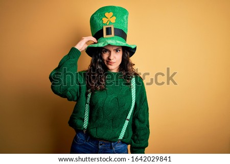 Beautiful curly hair woman wearing green hat with clover celebrating saint patricks day confuse and wonder about question. Uncertain with doubt, thinking with hand on head. Pensive concept.