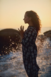 Beautiful curly woman by the ocean. Woman yoga portrait. Breathtaking sunset. Ocean splashes. Amazing graceful woman doing yoga by the ocean sunset. Yoga poses.