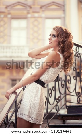 Beautiful curly woman in white dress on the metal stairs