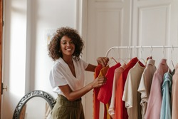 Beautiful curly young dark-skinned woman in white blouse and khaki shorts smiles sincerely, looks into camera and poses in dressing room.