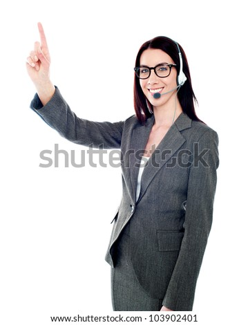 Beautiful customer care executive pointing up at copy space over white background