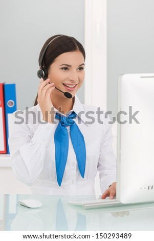 Beautiful customer service representative. Cheerful young female customer service representatives in headset working at the computer and smiling