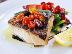 Beautiful cut of fish fllet as Baramundi or white seabass with dark skin grilled to juicy texture served with colorful assorted grilled vegetables red bell pepper drizzled with balsamic vinegar