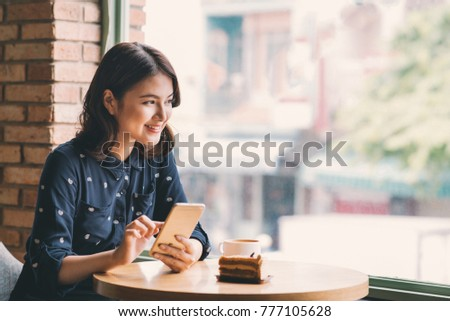 Beautiful cute asian young businesswoman in the cafe, using mobile phone and drinking coffee smiling