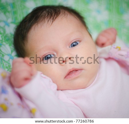 Beautiful cute baby girl is lying in a bed.