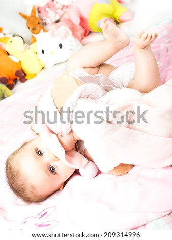 Beautiful cute baby with pink blankets and toys