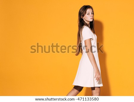 Beautiful Cute fashion girl teenage in white dress on yellow background with long hair posing happy #471133580