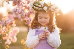 Beautiful cute kid girl 2-3 year old wear flower wreath over sunset and blooming cherry tree at background. Childhood. Spring season.