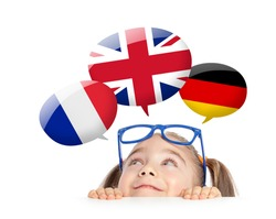 beautiful cute little girl hiding under table and curiously looking at the Uk, France and German flag speech balloons above her head. Learning English, French and German of K-12 student concept.