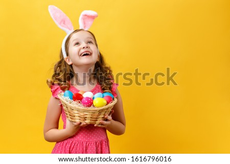 Beautiful cute little girl in Easter bunny ears holds a basket with eggs on a yellow background. The child raised his head and looks up. Copy space.
