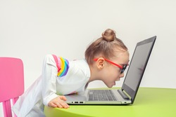 beautiful cute little girl looking at laptop screen very closely with open mouth. Shocked or surprised little girl on the internet in laptop computer on table.