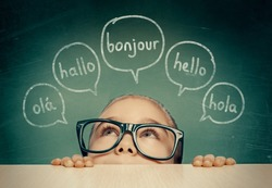 Beautiful cute little girl with eyeglasses hiding under table and looking at hello word in french, english, spanish, portuguese and german in speech balloons. K-12 foreign language learning concept.