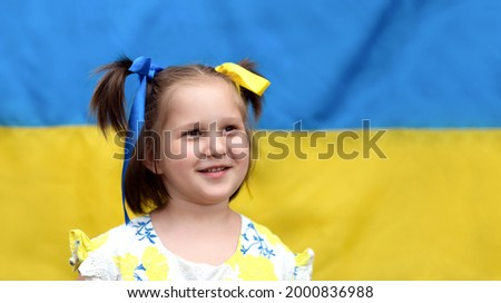 Beautiful cute smiling Ukrainian girl with ponytails with  ribbons on the background of the yellow-blue Ukrainian flag. Independence Day of Ukraine, Constitution Day, National Flag Day Photo stock ©