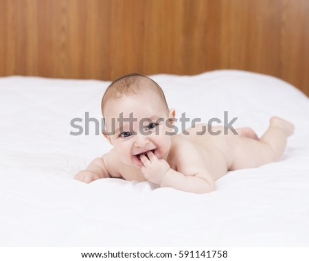 Beautiful cute teething baby biting fingers with funny expression, on white bed.