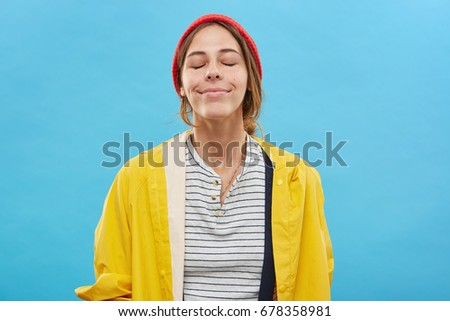 Shutterstock Beautiful cute young European female with happy smile, closing eyes in pleasure and enjoyment, enjoying nice smell. Pretty girl smiling, dreaming of something pleasant, having anticipated look