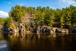 Beautiful Dalles of the St. Croix River looking across the river into St. Croix Falls, WI and the rugged cliffs with pine trees on a beautiful spring day at Interstate State Park.
