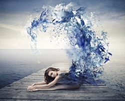 Beautiful dancer with a blue dress that becomes a wave of blue paint