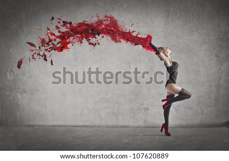 Beautiful dancer with a wake of red paint coming out from her hands