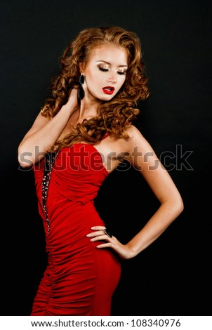 Beautiful, daring red-haired girl in a red dress on a black background