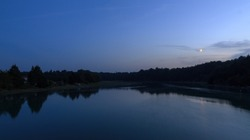 Beautiful dark blue nightscape landscape of the coastal river L'Arguenon after sunset with a new moon rising and reflection in the water near Saint-Malo in Brittany, France