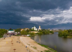 Beautiful dark blue thundercloud over the city. Top view of the city, churches, bridge, river. Aerial photography. The central beach of the city. People walk along the river.