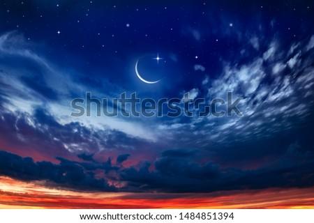 Beautiful dark fluffy cloudy sky with sun rays . Crescent moon with beautiful sunset background . Generous Ramadan . New moon. Prayer time.