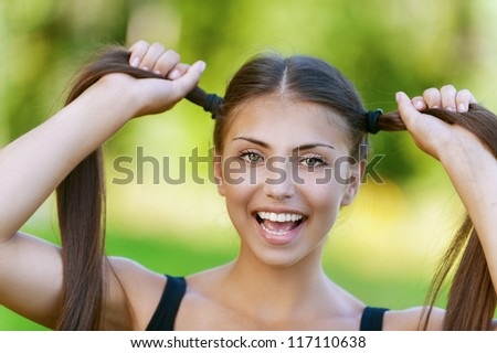 Beautiful dark-haired funny young woman holds up their tails, against background of summer green park.