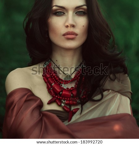 Stock Photo Beautiful dark-haired girl in a red coif was lost in the wild forest