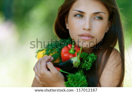 Beautiful dark-haired sad young woman holding vegetables - eggplant, peppers and parsley, against background of summer green park.