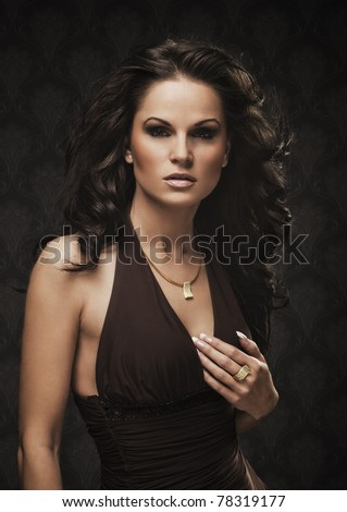 Beautiful dark haired woman in brown dress with golden ring and necklace with brilliants