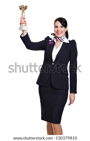 Beautiful dark haired young business woman dressed in a navy suit with a purple scarf and white shirt standing smiling and lifting a sports cup in the air, isolated on white background
