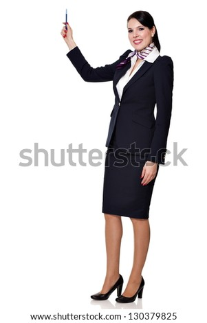 Beautiful dark haired young business woman dressed in a navy suit with a purple scarf and white shirt standing smiling and holding a pen in her lifted right hand, isolated on white background
