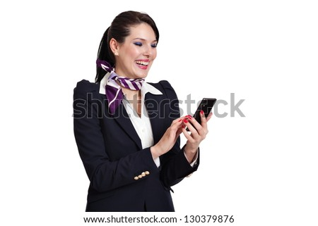 Beautiful dark haired young business woman dressed in a navy suit with white shirt and a purple scarf standing laughing checking her mobile phone, isolated on white background