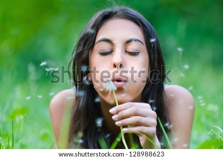 Beautiful dark-haired young woman lying on grass and blows away dandelion, against background of summer green park.