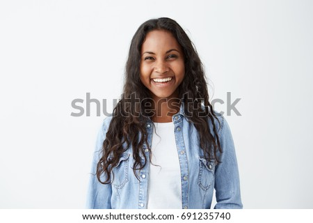 Beautiful dark-skinned female with long brunette hair and broad happy smile wearing denim shirt enjoying good positive news concerning her promotion at work, posing isolated against white blank wall