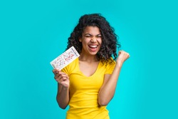 Beautiful dark skinned girl skreaming and laughing clenches her fist in winning gesture holding filled lottery ticket and celebrating victory. Lucky excited smiling young african woman hit a jackpot.