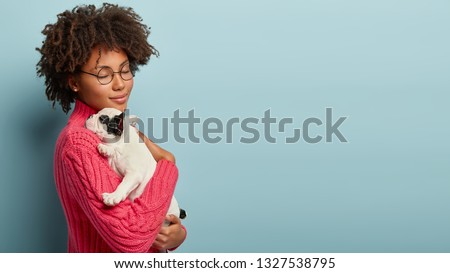 Beautiful dark skinned woman feels delighted, closes yes from pleasure, carries little baby dog with black and white colour, have fun at home, expresses tender emotions, care and love to small puppy #1327538795