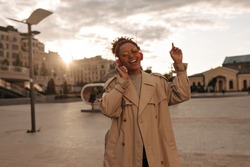Beautiful dark-skinned woman in beige trench coat sings and listens to music in red headphones outside during sunset.