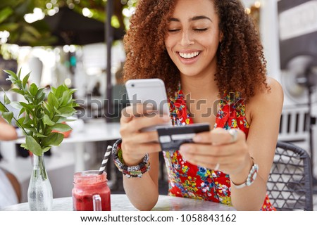 Beautiful dark skinned young female with cheerful expression, holds smart phone and credit card, banks online or makes shopping while sits against cafe interior. Payment and leisure concept.