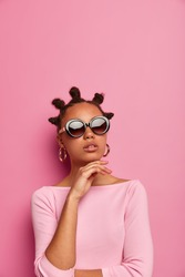 Beautiful dark skinned young woman keeps hand under chin, wears trendy summer sunglasses and stylish jumper, makes fashion photography, models in studio against pink background. Vogue, style