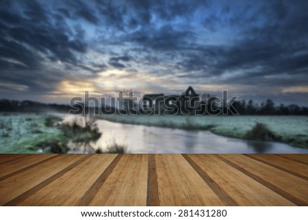 Beautiful dawn landscape of Priory ruins in countryside location with wooden planks floor