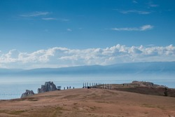 Beautiful day landscape with lake Baikal. Rock and Cape shaman against the blue sky and white clouds. Big brown beach with tourists. Russia, Khuzhir
