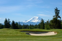 Beautiful day on a golf course, green fairway and bright sand trap with Mt Rainier in the background