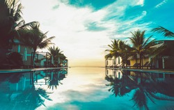 Beautiful day time at a beach resort in tropics. Perfect beach, relaxation pool in a luxurious beachfront hotel resort in day light perfect beach holiday vacation banner.