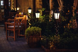 beautiful decor of lanterns and garlands outside in the garden cafe