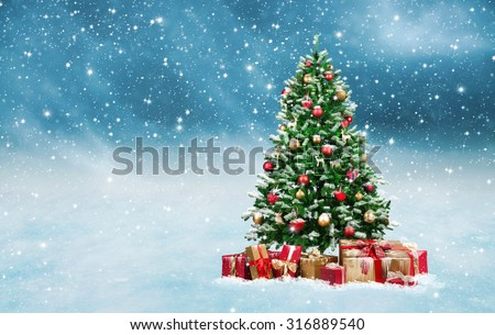 Stock Photo Beautiful decorated christmas tree with present boxes in a winter landscape with snow