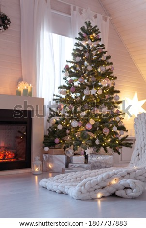 Beautiful decorated evergreen glowing fir tree with pastel color balls and garland lights near fireplace. Christmas cozy scandic decoration at wooden house. New Year Hygge cabin interior, no people.  Сток-фото ©