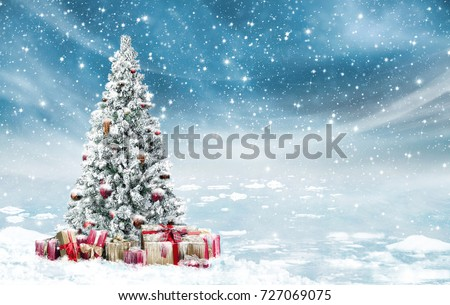 Stock Photo Beautiful decorated snowed in christmas tree in a cold winterlandscape