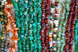 Beautiful decoration from beads of natural colored stones on market closeup