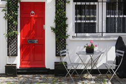 Beautiful decoration of grey round table, two chairs with pretty flowers on the table by windows and red wooden door outside building in sunny day